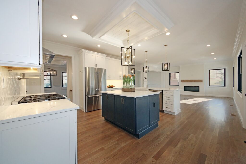 Kitchen designed with Homecrest custom cabinets in white with an added pop of color with blue floating island, making a beautiful and elegant kitchen
