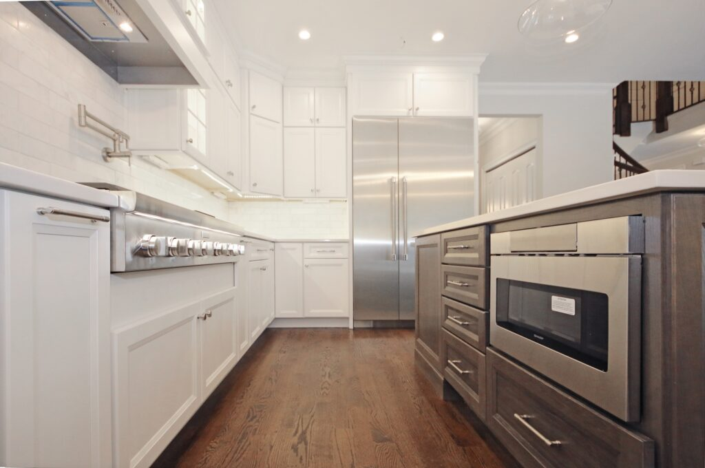 Custom kitchen design with white cabinets and a floating island with gray custom cabinets