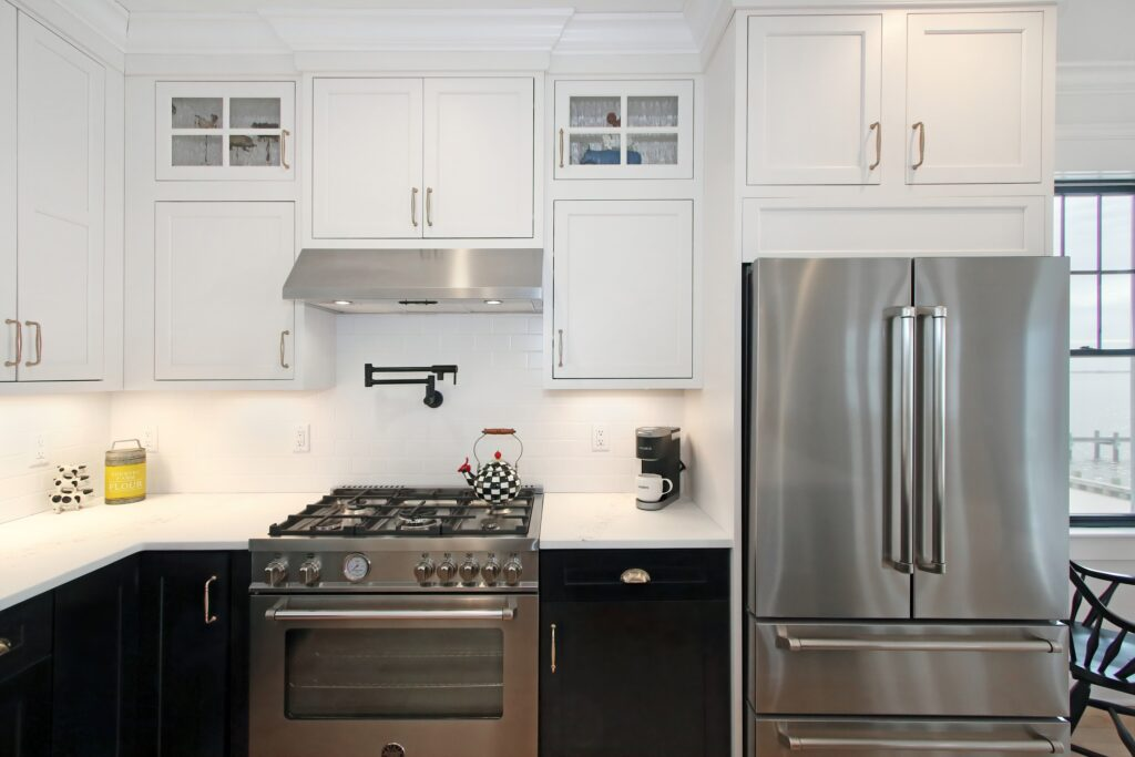 Custom kitchen cabinets with black and white combination, chrome appliances incorporated