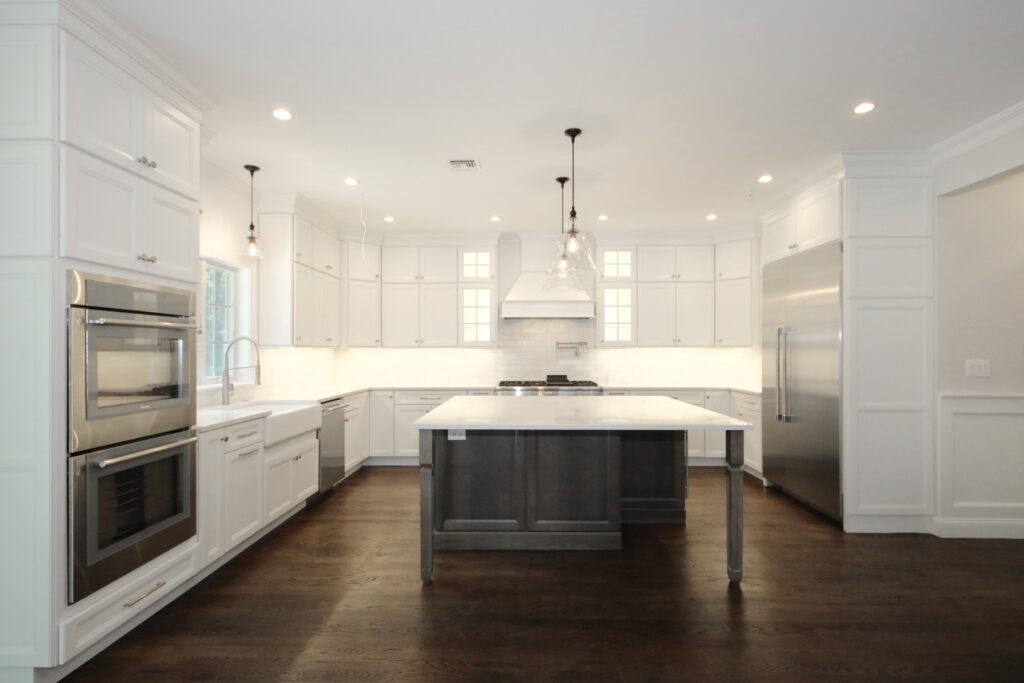 White Custom kitchen cabinets with floating island and wall oven