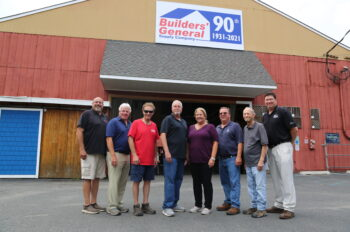 """8 Builders' General employees stand in front of the red and yellow building with a company sign above them saying """"90th"""" for their 90th anniversary."""